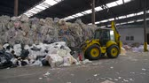 k opakovanému použití : Obuhov, Ukraine - Fedruary 2017: Logistics at the waste processing plant. Loader sorts the pallets with the recycled material at the waste processing plant. Footage with sound.