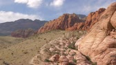 кактусы : People walk to Red Rock Canyon Nevada Las Vegas. Tourists hiking in Red Rock Canyon, Nevada, USA. Camera Pans - Red Rock Canyon Nevada. Scenic view, Red Rock Canyon State Park, Nevada, USA. Стоковые видеозаписи
