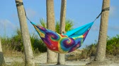 меньшинство : Lesbian couple relaxing in rainbow hammock at sunset. Two lesbians hid in a cozy hammock of rainbow colors on the beach. Young couple in love relaxing in hammock by beach. Lesbian couple retired.