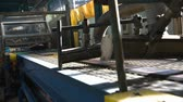 úsek : Manufacture of tires. Tyre production machine conveyor. Rubber tape at a tire factory is cut into pieces before forming in a curing machine. Camera tilted to the left. Dostupné videozáznamy
