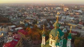 barok : Flying above and around St. Andrews Church in Kiev at sunset. Panorama of the city of Kiev with the domes of St. Andrew at sunset. The drone camera moves forward and flies over the domes of St. Andrew
