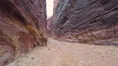 요르단 : Camera moves in Al Siq canyon, which goes to the ancient city of Petra. Walking inside the Al Siq Canyon towards the Treasury in Ancient City of Petra. Petra is archaeological city in southern Jordan.