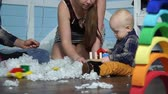 male animal : Parents sitting with his son in the artificial snow and play with wooden toys Stock Footage