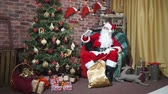 male animal : Santa waving his hand while sitting in a chair at the Christmas tree