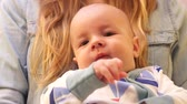 drooling : Close-up of baby chews her fingers while sitting on hands at mum