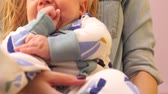 drooling : Close-up of little babys legs in pajamas sitting on hands at mum Stock Footage
