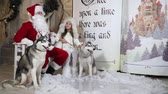 jev : Santa and little girl posing sitting on a bench with husky dogs