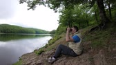Man looks through binoculars at the distance while sitting at the scenic river bank.