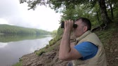 eko : Man looks through binoculars at the distance while sitting at the scenic river bank.