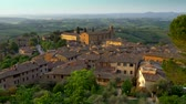 toskana : San Gimignano, Tuscany, Italy. Panning shot of San Gimignano medieval town roofs in sunset lights. UHD, 4K Stok Video
