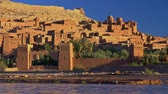 kasbah : Stone towers and buildings in ksar of Ait-Ben-Haddou - an ancient fortified village along the former caravan route between the Sahara and Marrakech in present-day Morocco. Sunset time. 4K, UHD Stock Footage