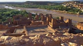 марокканский : Clay houses of Ait Ben Haddou, Morocco near Ouarzazate in the Atlas Mountains. Ait Ben Haddou is a fortified village (ksar) along the former caravan route between the Sahara and Marrakech. UHD Стоковые видеозаписи