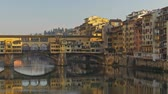 toszkána : Florence, Italy. Panoramic shot of the Ponte Vecchio bridge. Its Medieval bridge over the Arno River. The bridge has shops situated on it. 4K Stock mozgókép
