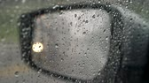 bande : Rain drops on car window and mirror during rain. Defocused traffic lights on the mirror Vidéos Libres De Droits