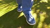 dürtmek : Man in blue denim jean shoes walking on green moss in the park Stok Video