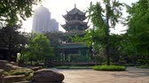 pavilion : Chengdu, Sichuan, China. Walking in the Wangjiang Pavilion Park lit by warm rays of sun. Wangjiang Tower (Wangjiang Pavilion) and beautiful green flora are seen in the background. 4K