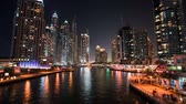 освещенный : DUBAI, UAE - SEPTEMBER 21, 2014: Timelapse view of Dubai Marina skyscrapers with yachts and boats