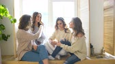 drby : four beautiful girls discuss smile sitting on window. Girlfriends having fun and laugh in bedroom Dostupné videozáznamy