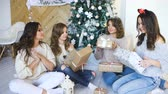 at home : Smiling girlfriends present gifts each other. Christmas mood Stock Footage