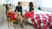 постельные принадлежности : Four beautiful girls have gossip talks while sitting on bed Women having fun laugh in bedroom.
