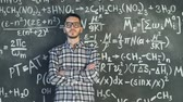 chalk : Young scientist man posing in chemical and mathematical equations wall room interior