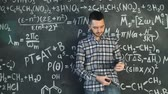 kimya : Young scientist man clean his glasses in chemical and mathematical equations wall room interior Stok Video