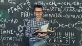científico : Young scientist man read book in chemical and mathematical equations wall room interior