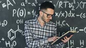 chalk : Young scientist man read book in chemical and mathematical equations wall room interior