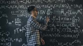 professor : Young scientist man write chock in chemical and mathematical equations wall room interior
