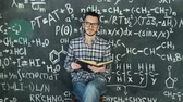 teoria : Young scientist man read book in chemical and mathematical equations wall room interior