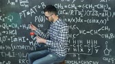 teoria : Young scientist man make laboratory experiment in chemical and mathematical equations wall room
