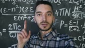 chalk : Young scientist man making selfie shoot in chemical and mathematical equations wall room interior Stock Footage