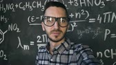 kimya : Young scientist man making selfie shoot in chemical and mathematical equations wall room interior Stok Video