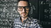 científico : Young scientist man making selfie shoot in chemical and mathematical equations wall room interior Vídeos