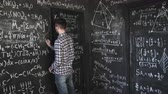 professor : Young scientist man write chock in chemical and mathematical equations wall room interior timelapse Vídeos