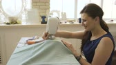 costurar : Young clothing designer and seamstress woman work with sewing machine in tailor studio