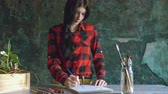 глубина : Young woman artist painting scetch on paper notebook with pencil Стоковые видеозаписи