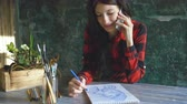 глубина : Young woman artist painting scetch on paper notebook with pencil. Girl smile and talks phone