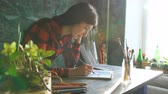 suluboya : Young woman artist painting scetch on paper notebook with pencil. Bright sun flare from window