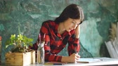 suluboya : Portrait young woman artist painting scetch on paper notebook with pencil Stok Video