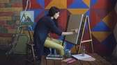 глубина : Young woman artist draw scetch wit pencil on easel canvas, preparing to paint picture Стоковые видеозаписи
