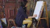 suluboya : Young woman artist draw scetch wit pencil on easel canvas, preparing to paint picture Stok Video