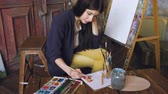 tuval : Young woman artist draw pictrure with watercolor paints and brush on easel canvas