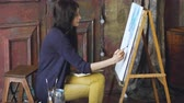 figura : Young woman artist draw pictrure with watercolor paints and brush on easel canvas