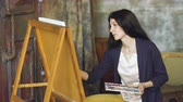hloubka : Young woman artist draw pictrure with watercolor paints and brush on easel canvas