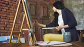suluboya : Young woman artist draw pictrure with watercolor paints and brush on easel canvas