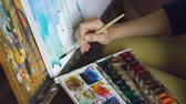 глубина : Young woman artist draw pictrure with watercolor paints and brush on easel canvas closeup hand