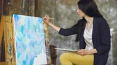 глубина : Young woman artist draw pictrure with watercolor paints and brush on easel canvas