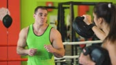 fitness : Kickboxing trainer man train with young woman in boxing ring