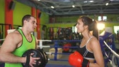 workout : Young woman boxer talks to man trainer smiling in boxing club